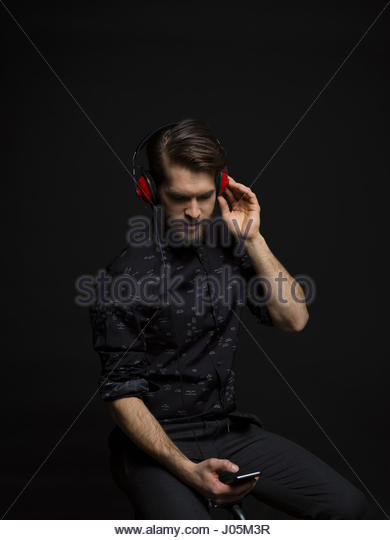 Brunette man listening to music with headphones and mp3 player against black background - Stock Image