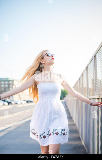 Knee figure of young handsome caucasian long blonde straight hair woman walking in the city, overlooking left, feeling - Stock Image