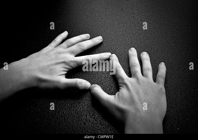 Two hands creating a heart shape on wet wood background - Stock-Bilder