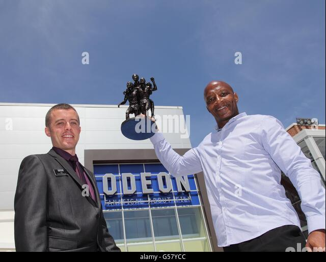 West Bromwich Albion star Cyrille Regis receives a commemorative statuette from Carl Fletcher of Odeon Cinemas  - Stock Image