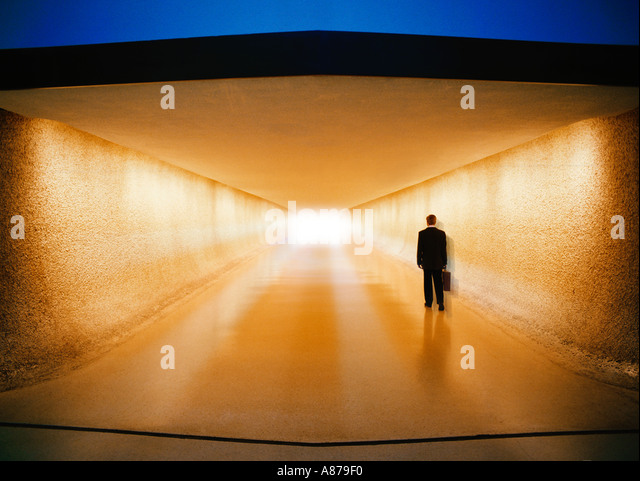 Businessman with briefcase walking down corridor toward baggage claim and ground transportation at an airport - Stock-Bilder