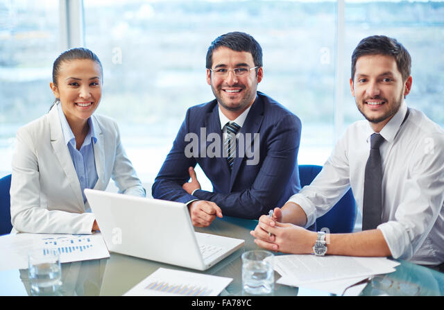 Portrait of a positive team sitting at a table - Stock Image