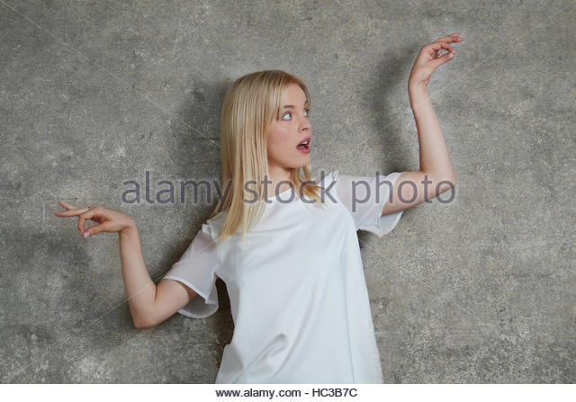 Portrait of young woman in front of concrete wall. - Stock-Bilder