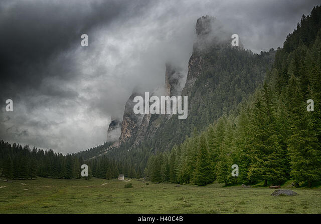 Green valley and clouds over the top of the mountains of Vallunga in a rainy summer day, italian alps - Stock Image