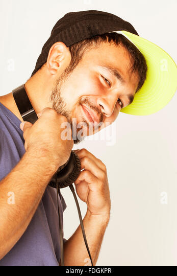 young asian man in hat and headphones listening music on white background - Stock Image