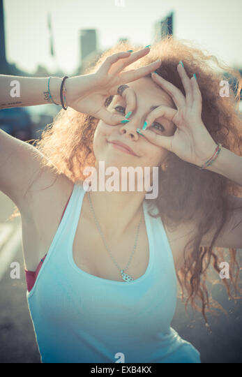 young beautiful long curly hair hipster woman in the city - Stock Image