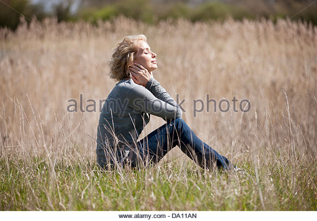 A mature woman sitting on the grass, enjoying the sunshine - Stock Image