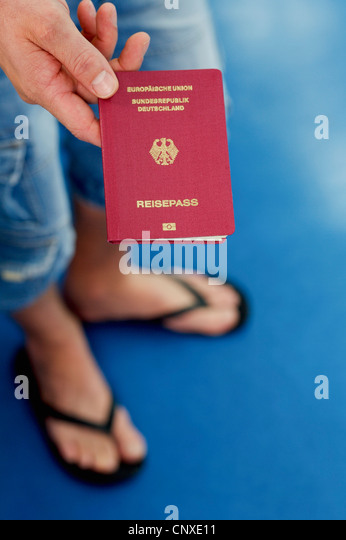 Detail of a man holding a German passport - Stock Image