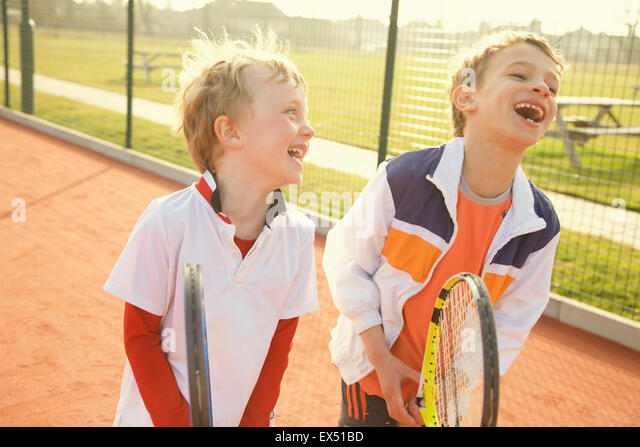 Two Young Boys Holding Tennis Rackets Smiling - Stock Image
