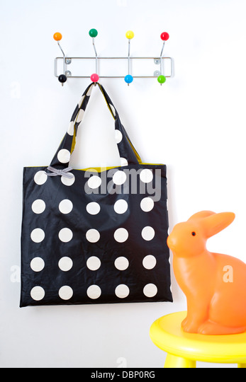 Bag hanging on coat rack, rabbit lamp in foreground, Munich, Bavaria, Germany - Stock Image
