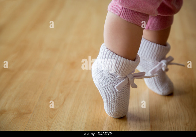 Baby girl in pink booties - Stock Image