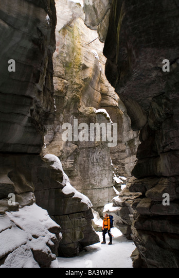 Female climber explores ice climbing in the narrows of Maligne Canyon in Jasper National Park, Alberta, Canada - Stock Image