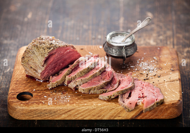 Roast beef on cutting board and salt cellar - Stock Image