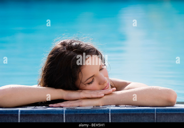 Young woman napping at the poolside - Stock-Bilder