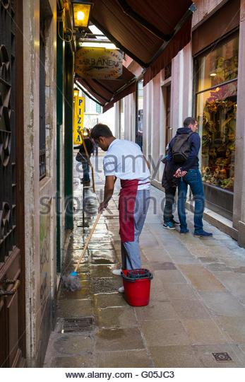 Resturant worker washing down pavement prior to opening, Venice, Italy, April - Stock-Bilder