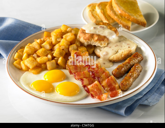 A power country breakfast with three eggs, bacon, sausage, potato, biscuits and gravy and toast - Stock Image