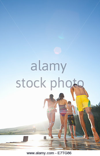 Family running  on wooden dock at lake - Stock Image