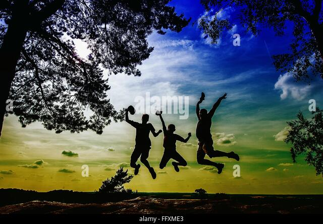 Silhouette People Jumping On Landscape - Stock Image