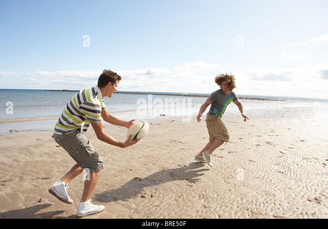 Two Teenage Boys Playing Rugby On Beach Together - Stock Image