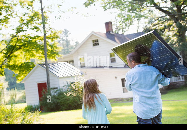 A man carrying a solar panel towards a building under construction. - Stock Image