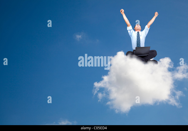 young businessman with computer sitting on the cloud - Stock-Bilder