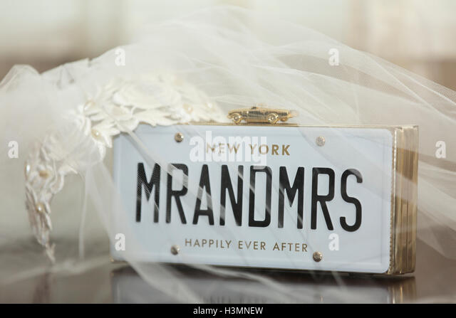 Bridal veil with Mr and Mrs placard surmounted with a gold model car with the words Happily Ever After below celebrating - Stock Image