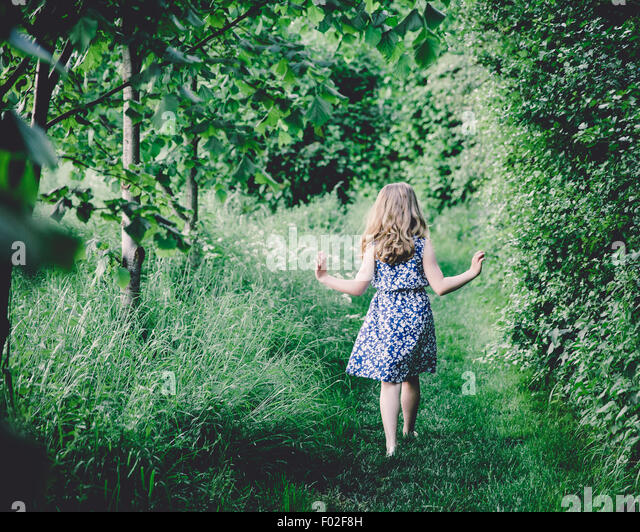 Rear view of a girl walking through forest - Stock Image