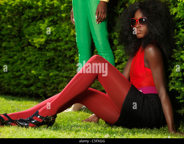 Young stylish black woman in fancy bright clothes sitting on the grass in a park - Stock Image