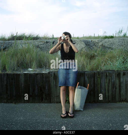 Young woman by the sea taking a picture - Stock Image