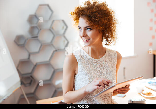 Cheerful cute curly young business woman standing and using tablet in office - Stock Image
