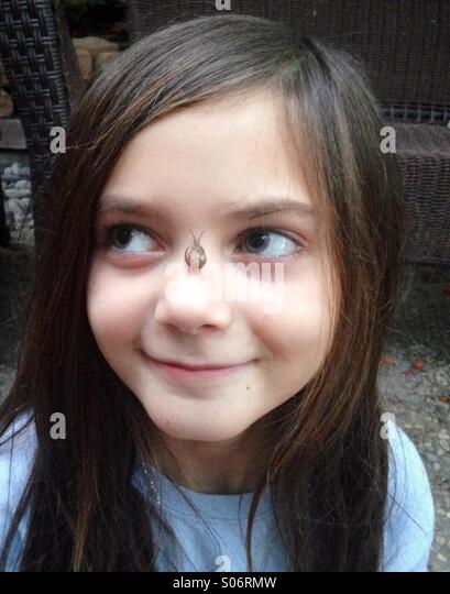 A young adorable girl smiles with a small snail on her nose. - Stock-Bilder