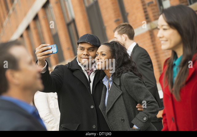 People keeping in contact using mobile phones A man holding out a camera phone and taking photograph - Stock Image