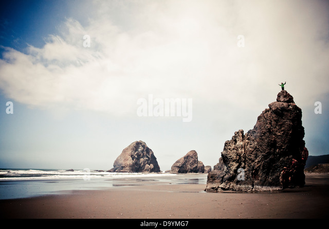A climber stands on a monolith in Pistol River State Park on the Oregon Coast, USA. - Stock Image