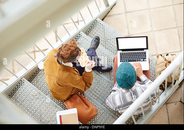 Hipster couple using computer and eating lunch sitting in stairs at university campus - Stock-Bilder