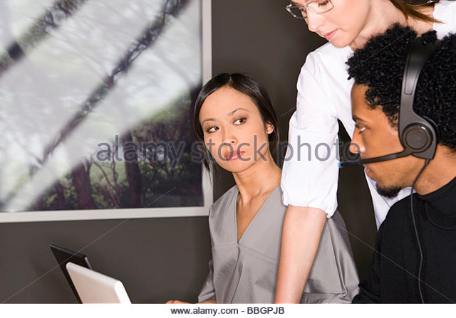 Young Asian businesswoman looking at African man office - Stock Image