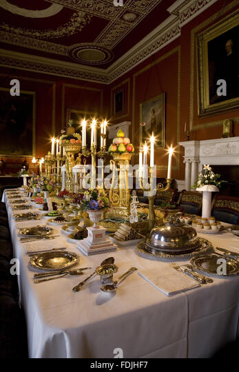 The Dining Room at Attingham Park, Shrewsbury, Shropshire, with the dining table laid for a formal dinner and with - Stock-Bilder