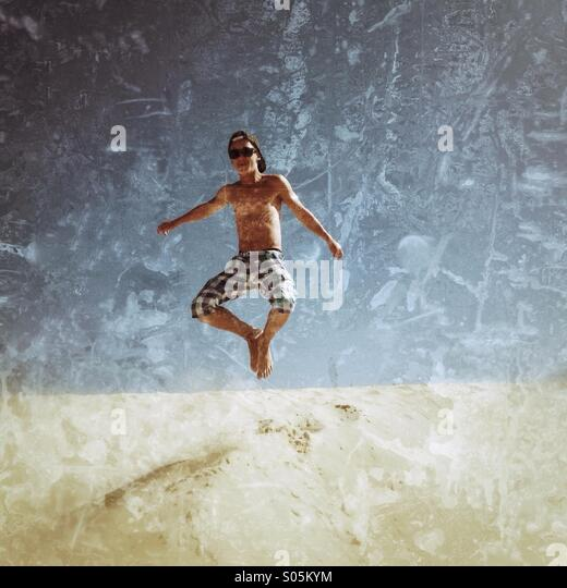 Boy jumping in Tarifa dunes. - Stock Image