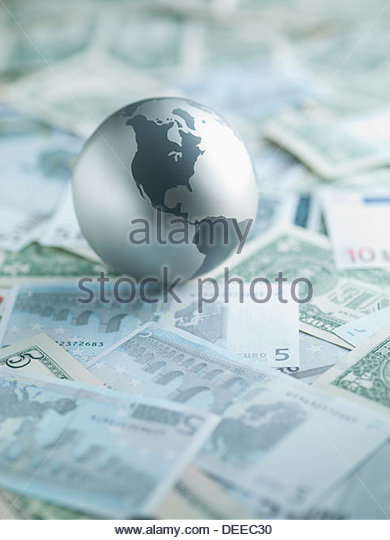 Metal globe resting on paper currency - Stock Image