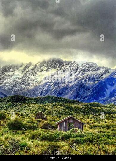 Small hut at the foot of surrounding mountains near Mt Cook in New Zealand - Stock Image