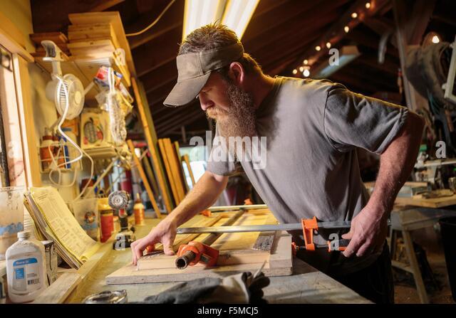 Wood artist working in workshop - Stock Image