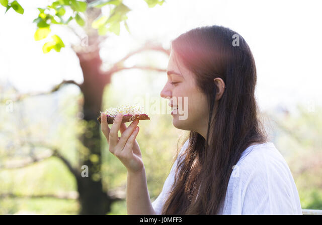 Teenage girl eating rye bread with beetroot cream and alfalfa sprouts - Stock Image