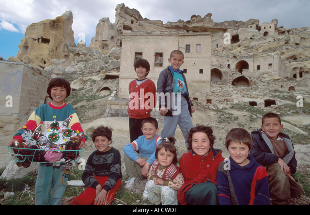 Turkey Cappadocia Goreme Valley kids near volcanic tufa mound cave dwellings - Stock Image