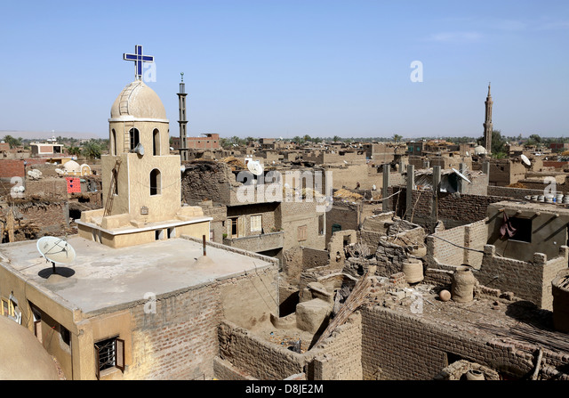 Christian cross on a coptic church and cresent on the minaret of a muslim mosque in Upper Egypt - Stock-Bilder