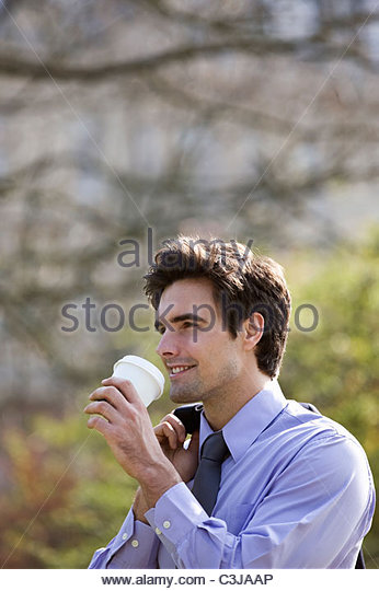 A businessman drinking from a paper cup - Stock Image