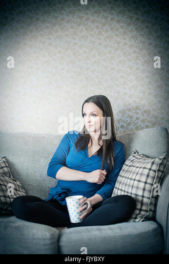 young woman resting on sofa bed with cup of tea - Stock Image