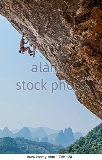 Male climber climbing at Odin's Den next to Moon Hill in Yangshuo, Guangxi Zhuang, China - Stock Image