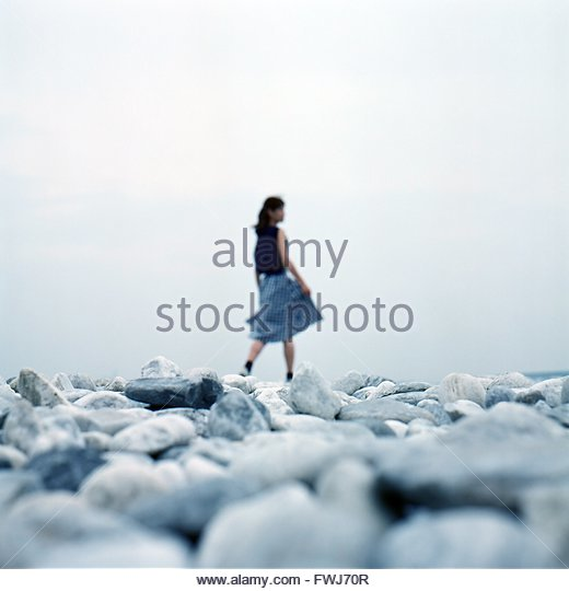 Surface Level Of Woman Walking On Pebble Beach - Stock Image