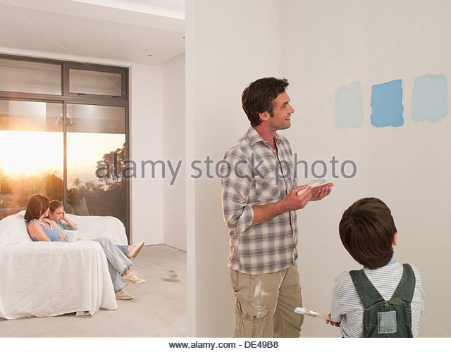 Father and son looking at paint samples on wall - Stock Image