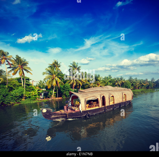 Vintage retro hipster style travel image of Kerala travel tourism background - houseboat on Kerala backwaters. Kerala, - Stock Image
