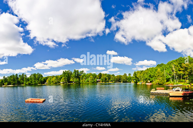 Beautiful lake with dock and diving platform in Ontario Canada cottage country - Stock Image